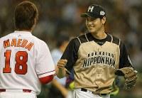 オールスターゲームで三塁コーチだった広島の前田健太(手前)とタッチして笑顔の日本ハム・大谷翔平=東京ドームで2015年7月17日、山本晋撮影