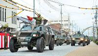 機動車に乗って行進する陸上自衛隊員=京都府福知山市の広小路通りで、佐藤孝治撮影