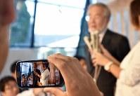 ノーベル医学生理学賞受賞決定から一夜明け、大勢の記者に囲まれながら質問に答える大隅良典・東京工業大栄誉教授(中央奥)の様子が映し出されるスマートフォンの画面=東京工業大大岡山キャンパスで2016年10月4日午前6時46分、宮間俊樹撮影