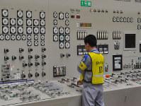 川内原発の中央制御室で1号機の発電設備と送電系統を切り離して発電停止作業をする九州電力の担当者=九電提供