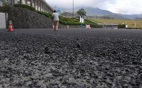 Ash deposits are scattered on the ground of a youth exchange facility in Aso, Kumamoto Prefecture, on Oct. 8, 2016. (Mainichi)