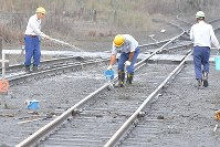 Railway workers wash away volcanic ash that piled up on the tracks near Miyaji Station on the JR Hohi Line in Aso, Kumamoto Prefecture, on Oct. 8, 2016. (Mainichi)