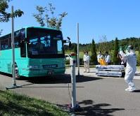 放射性物質の付着を調べるため、検知機器を備えた2本のポールの間を通るバス