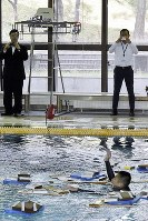災害時を想定した実験で、おぼれている人に近づき、GPSがついた赤い浮輪を投下するドローン(左上)=東京都渋谷区の東京消防庁消防学校で2016年10月12日午前10時5分、北山夏帆撮影