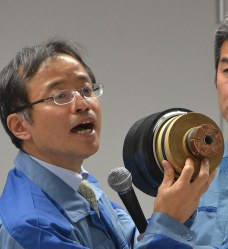 A TEPCO representative shows a power cable that runs underground, the same type as the one that caught fire, during a news conference at TEPCO headquarters on Oct. 12, 2016. (Mainichi)
