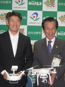 ドローン事業の概要を発表する、あきる野市の沢井市長(右)