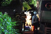 電車(右)の横でつぶされたようになった乗用車を調べる捜査員や消防隊員ら=16日午後10時54分