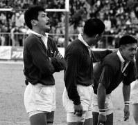 全国社会人ラグビーで7連覇を達成し、喜ぶ同僚の横で天を仰ぎ、涙をこらえる平尾選手(左)=秩父宮ラグビー場で1995年1月8日