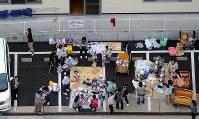 防災ずきんをかぶって保育園の駐車場に避難する園児や保護者ら=鳥取県倉吉市で2016年10月21日午後3時56分、本社ヘリから貝塚太一撮影