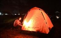 余震が続くため、駐車場にテントを張って夜を明かす女性。熊本地震発生当初の報道を見て、災害時に役に立つかもしれないとテントを買って備えていた。女性は「『まさかの時』が来るとは思ってもいなかった」と話した=鳥取県北栄町下神で2016年10月21日午後7時16分、山崎一輝撮影