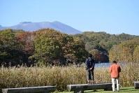 鏡大沼のほとりに立って樽前山(後方)や色づき始めた紅葉を楽しむ行楽客=北海道苫小牧市錦岡の鏡大沼公園で2016年10月19日、福島英博撮影