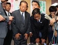 衆院東京10区補選で当選を決めてから一夜明け、自民党本部で二階俊博幹事長(中央左)と並んで取材に応じ、一礼する若狭勝氏(同右)=自民党本部で2016年10月24日午前10時34分、小川昌宏撮影