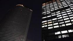 午後10時に一斉消灯された電通の本社ビル(左)=2016年10月24日、猪飼健史撮影