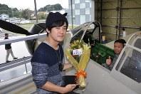 来場40万人目となった佐藤良久さん(右)と花束を持つ長男武尊さん=阿見町廻戸の予科練平和記念館で