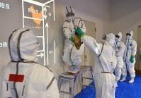 高病原性鳥インフルエンザの防疫演習で、防護服で訓練する県などの職員=佐久市の県佐久合同庁舎で