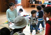 双子のお母さんたちに笑顔で声をかける山岸和美さん(左奥)=金沢市額新保1で、山口敬人撮影