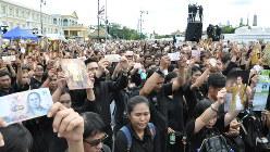 王室賛歌に合わせてプミポン国王の写真などを掲げる人々=タイ・バンコクの王宮前で2016年10月22日、西脇真一撮影