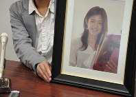 亡くなった妻の梨絵さんの遺影を手に会見する夫。梨絵さんにプロポーズした時に撮影した写真という=横浜市で2016年10月27日午後1時30分、藤沢美由紀撮影