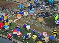 Colorful hot air balloons float up into the air in Saga on Oct. 31, 2016. (Mainichi)