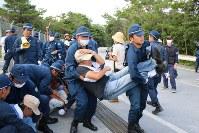 抗議の座り込みの市民を強制排除する機動隊員=沖縄県東村高江で10月26日