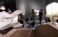 Children take in an object on display during a preview of the exhibition titled