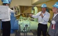 水力発電の説明を受ける奥ノ木信夫川口市長(右)=埼玉県川口市の横曽根浄水場で2015年5月28日