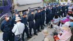 砂利搬入の間、抗議の市民に対峙して整列する機動隊=沖縄県東村高江で2016年10月27日、井田純撮影