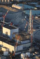 建屋カバーの撤去作業で壁パネルが取り外された福島第1原発1号機(中央)。手前は取り外された壁パネル=2016年11月4日午前6時17分、本社機「希望」から