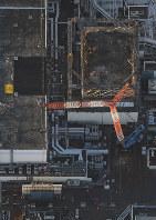 建屋カバーの撤去作業で壁パネルが取り外された福島第1原発1号機(右上)。左下は取り外された壁パネル=2016年11月4日午前6時22分、本社機「希望」から