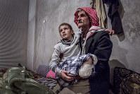 倉庫の中で毛布などを床に敷いて暮らすムスタファさん(右)とファデル君=2014年12月1日、トルコ・スルチで写真家の川畑嘉文さん撮影