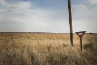 トルコとシリア国境にある緩衝地帯。地雷が敷設してあることを示す看板(右手前)が立てられているが、危険を承知で渡るシリア人も多い=チョンバンベイで2012年10月2日、写真家の川畑嘉文さん撮影