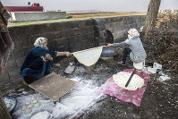 難民キャンプの外で暮らすシリア人女性。パン(ホブス)を焼いている。原料となる小麦粉は支援団体などから受け取った=2014年12月6日、トルコ・スルチ郊外で写真家の川畑嘉文さん撮影