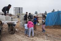 シリアから逃れてきた人たちのために、資材などを準備するトルコ人たち。無償でテントを提供する親切な人々もいる=トルコ・スルチで2014年12月1日、写真家の川畑嘉文さん撮影