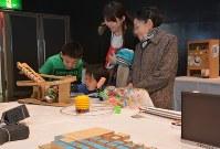 展示された発明品を熱心に見入る家族連れ=秋田市で
