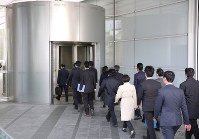 新入社員が過労自殺し労災と認定された問題で電通本社に労働基準法違反容疑で家宅捜索に入る東京労働局と三田労働基準監督署の職員=東京都港区で2016年11月7日午前9時26分、後藤由耶撮影