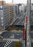 A large hole is seen in a road in front of JR Hakata Station in Hakata Ward, Fukuoka, on Nov. 8, 2016. (Mainichi)