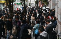 A road is seen crowded with people blocked from their usual commute or kept out of buildings by a large hole that opened in the road, in Hakata Ward, Fukuoka, on Nov. 8, 2016. (Mainichi)