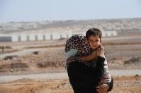 約3万6000人のシリア難民が暮らすアズラック難民キャンプで長男アマールちゃん(4)を抱きしめるサーミア・アルアリさん(37)。空爆が続くアレッポから逃れてきた。「古里には何も残っていない。未来を思い描くことさえできない」=ヨルダン・ザルカ県で2016年10月6日、久保玲撮影