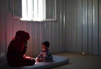 薄暗いコンテナの中で過ごすサーミア・アルアリさんと長男アマールちゃん。10畳ほどの室内には家具や生活用品はほとんどない=ヨルダン・ザルカ県のアズラック難民キャンプで2016年9月29日、久保玲撮影