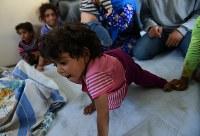 コンテナの中で両腕を使って、左足を引きずりながら移動するゼイナブちゃん=ヨルダン・ザルカ県のアズラック難民キャンプで2016年10月4日、久保玲撮影