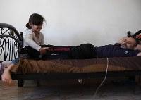 内戦で負傷し、下半身が不自由になったムハンマド・ディアブさん(41)にマッサージをする娘のバトゥールちゃん(7)。看護師をまねて自ら始めた。医師になって父のようなけが人を治すことが夢だ=ヨルダン・アンマンで2016年9月11日、久保玲撮影