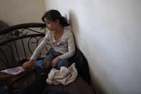父のムハンマド・ディアブさんのベッドに座るバトゥールちゃん。末娘のバトゥールちゃんは普段から父のベッドで過ごすことが多い=ヨルダン・アンマンで2016年9月11日、久保玲撮影