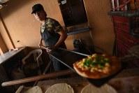 左足が不自由な父に代わりパン屋で連日12時間近く働く14歳の少年。きびきびと働く姿は大人と見間違う=ヨルダン・ザルカで2016年10月11日、久保玲撮影