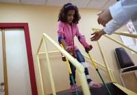 骨折した左脚のリハビリに励むリマールちゃん。ヨルダンに移住後、手術を5回受けたが完治する保証はない=ヨルダン・アンマンで2016年10月12日、久保玲撮影