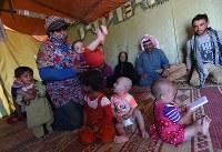 家族20人でヨルダンに避難したスレイマン・アルハサンさん(64・奥右から2人目)一家。シリアにいた時のように農業で生計を立て、テントで暮らしている=ヨルダン・アンマンで2016年10月5日、久保玲撮影