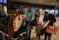 空港の搭乗ゲートに向かうフセイン・カリームさん一家。長男カリームさん(12・中央)は「アメリカには行ってみたい。でも二度とシリアに戻れなくなるかもしれない」と複雑な気持ちを話した=ヨルダン・アンマンのクイーンアリア国際空港で2016年10月11日、久保玲撮影