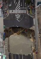 大規模に陥没したJR博多駅近くの道路=福岡市博多区で2016年11月8日午前9時42分、本社ヘリから須賀川理撮影