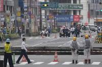 大きく陥没した道路の前で警戒に当たる警察官ら=福岡市博多区で2016年11月8日午前8時46分、須賀川理撮影