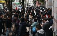 通行止めを迂回する通勤客やビルに入れない人たちで混雑する通り=福岡市博多区で2016年11月8日、須賀川理撮影