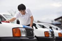 両親から受け継いだ会社のタクシーを磨く菅野真彦さん=岩手県陸前高田市で、猪飼健史撮影